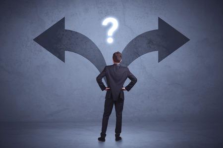 Geschäftsmann, der eine Entscheidung beim Betrachten von Pfeilen auf dem Wandkonzepthintergrund trifft