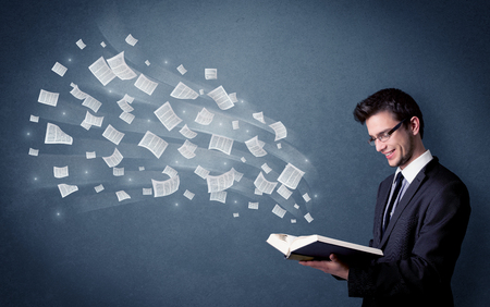 Casual young man holding book with pages flying out of it Archivio Fotografico
