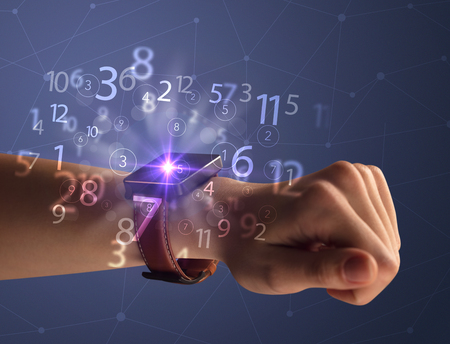 Close up female naked hand wearing smartwatch and numbers around Stockfoto