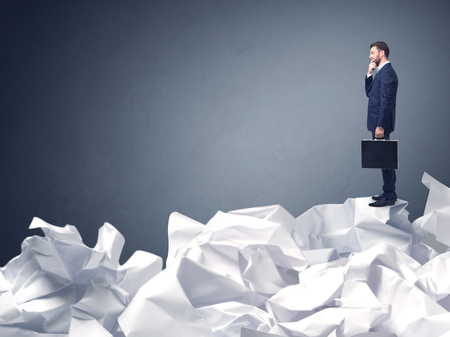 Thoughtful young businessman standing on a pile of crumpled paper with a blueish grey background Stock Photo