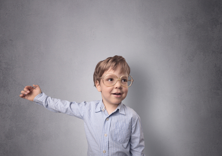 Adorable little boy portrait with empty grey wall background Stock Photo
