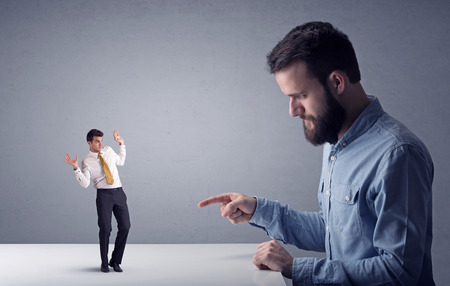 Young professional businessman being angry with an other miniature businessman in front of a grey background