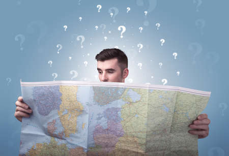Handsome young man holding a map with white question marks above his head Stock Photo