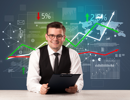 Young handsome businessman sitting at a desk with stocks and progress charts behind him Stock Photo