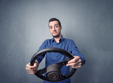 Young man holding black steering wheel on a blueish gray background Stock Photo