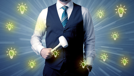 Better-looking businesman holding tool with idea bulbs concep Imagens