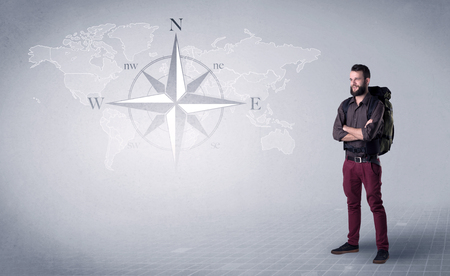 Handsome young man standing with a backpack on his back and a compass and a world map in the background Stock Photo