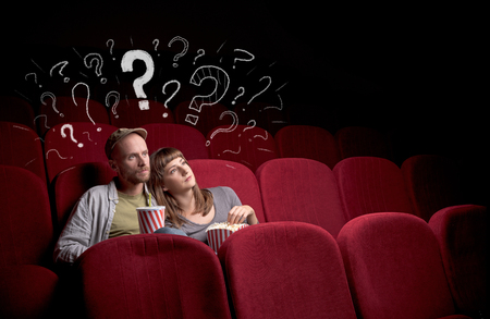 Nice couple in cinema with drawn question signs around Stock Photo