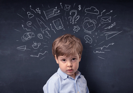 Smart little kid in front of a drawn up blackboard ruminate Stock Photo