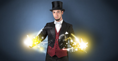 Magician holding his sparkling power between his two hand