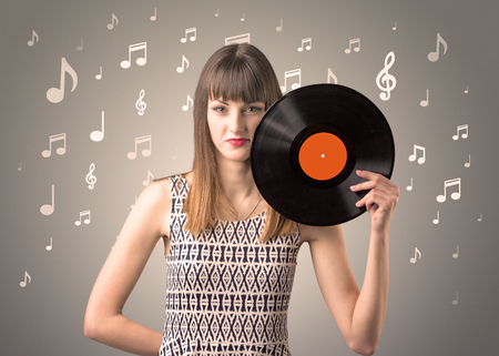 Young lady holding vinyl record on a brown background with musical notes behind her Stock Photo
