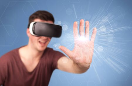Young impressed man wearing virtual reality goggles with blue hexagons around him