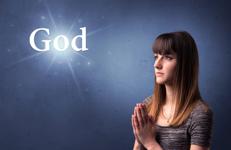 Young woman praying on a blue background with the word God written above her