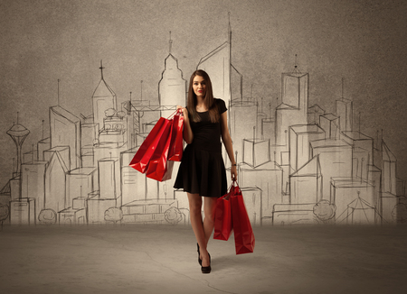 An attractive young lady standing with red shopping bags in front of drawn city landscape silhouette concept Stock Photo