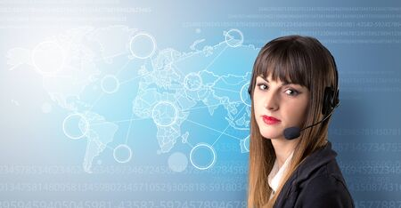 Young female telemarketer with blue background and world map and numbers behind her Stock Photo