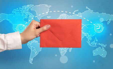 Female hand holding coloured and white envelope with blue map on the background