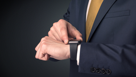 Man wearing suit with smartwatch on his wrist. Stock Photo