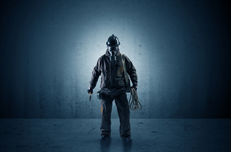 Bad agent in a dark room with arms on his hand and gas mask