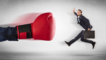 Big red boxing gloves hitting little businessman concept Stock Photo