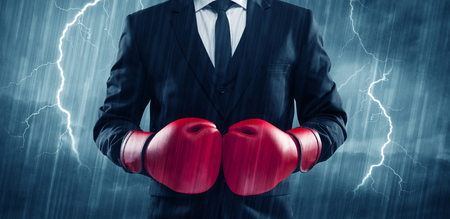 A dangerous sales person getting ready for a fight concept with red boxing gloves and thunder lightning in background. Фото со стока