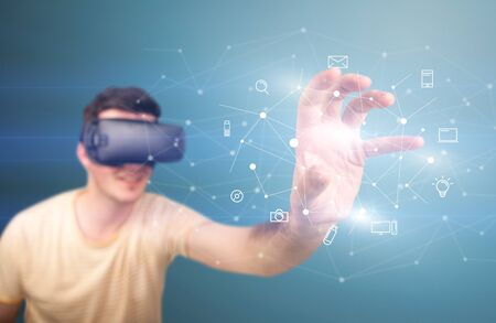 Young impressed man wearing virtual reality goggles with mixed media icons around his finger Stock Photo