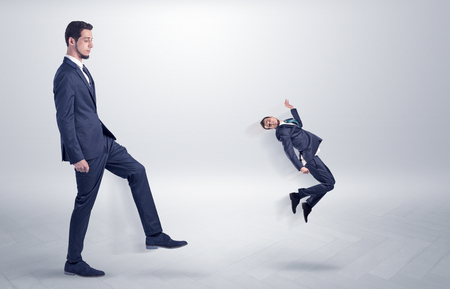 Small man fired by boss with white wallpaper Stock Photo