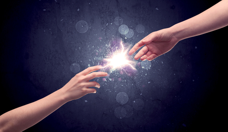 Hands reaching to light a spark Banco de Imagens