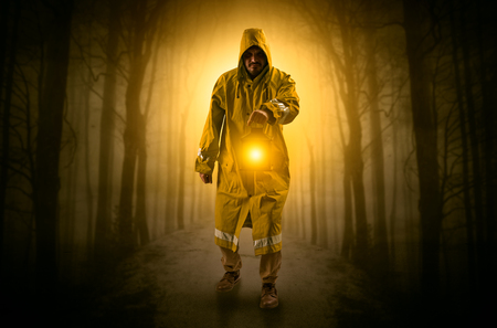Mysterious man coming from a path in the forest with glowing lan