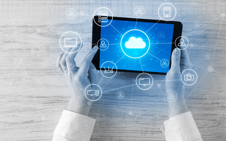 Hand using tablet with centralized cloud computing system concep