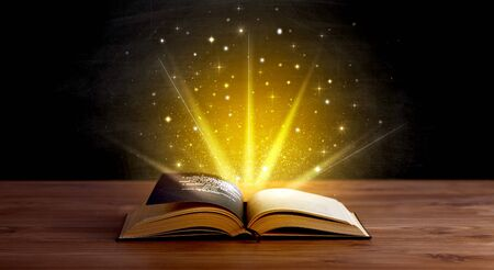 Yellow lights and sparkles coming from an open book  Stock Photo