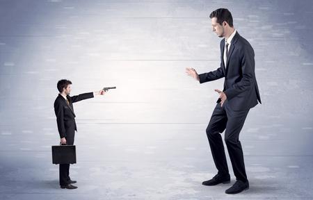 Small businessman shooting giant businessman Stock Photo