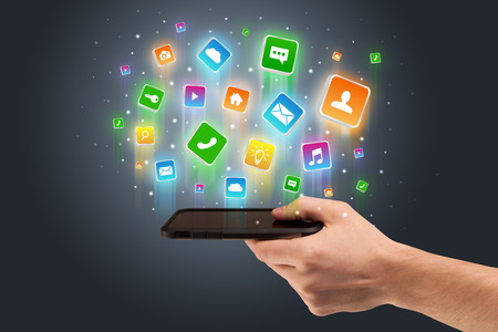 Hand using phone with application icons flying around Stock Photo