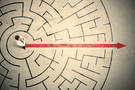 Business person standing in the middle of a circular maze