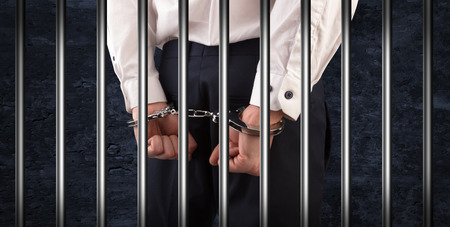 Close handcuffed man in jail Stockfoto