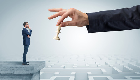 Little businessman from the top of the labyrinth thinking about strategies Stock Photo