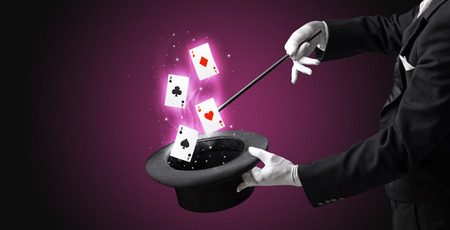 Magician making trick with wand and playing cards Stock Photo
