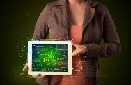 Casual young woman holding tablet with strategy and business related graphics