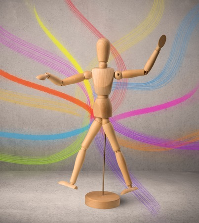 Wooden mannequin posed in front of a greyish background with colorful lines behind it