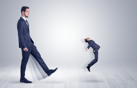 Giant businessman kicking out little businessman