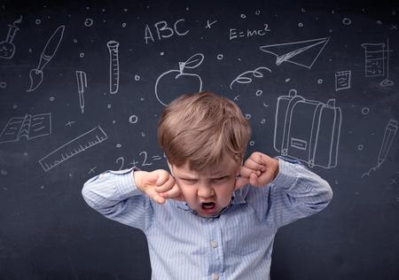 Little boy in front of a drawn up blackboard Stock fotó