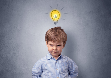 Little boy mull over with bulb above his head Stock Photo