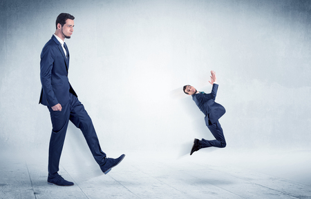 Big businessman kicking small businessman