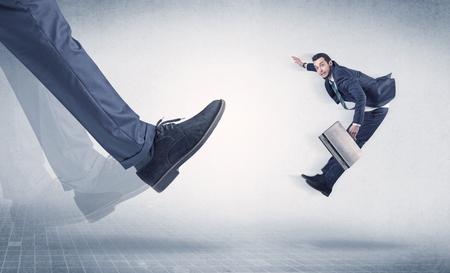 Businessman foot kicking small businessman