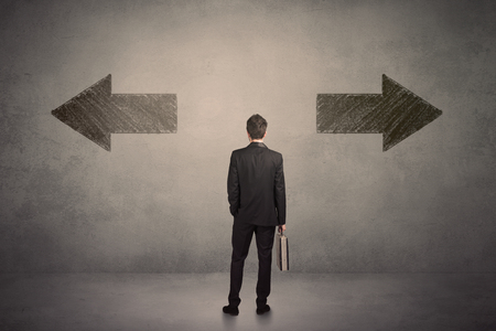 Business man taking a decision while standing in front of two grungy arrows on wall