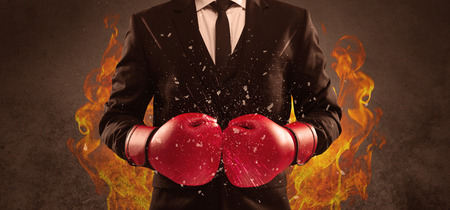 A strong sales person breaking something into pieces with red boxing gloves concept illustrated with glowing residue flying in the air. Фото со стока