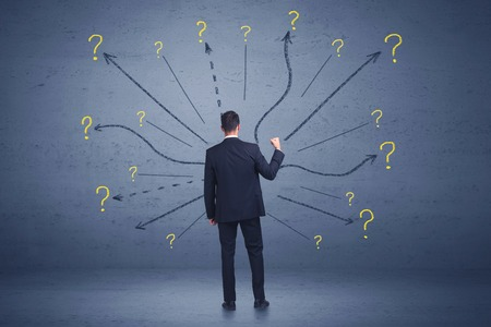 Businessman standing in front lines and question mark signs concept
