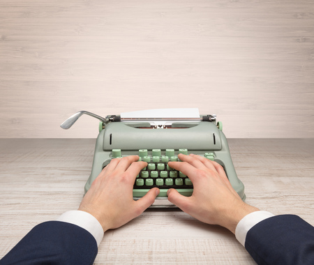 First person perspective elegant hand writing on an oldschool typewriter with copyspace Banco de Imagens - 100226419