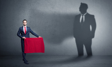 Businessman with toreador concept and his shadow on the background Imagens