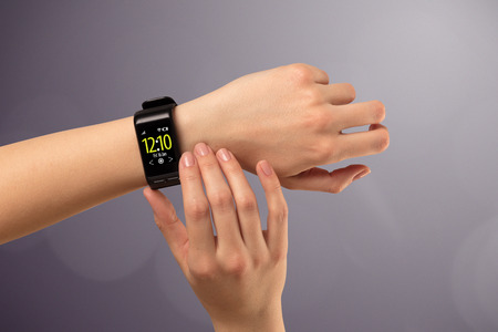 Female hand wearing and pressing smartwatch Standard-Bild