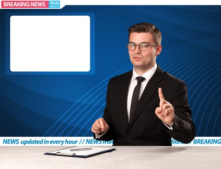 Television reporter telling breaking news at his studio desk with copy space Stock Photo